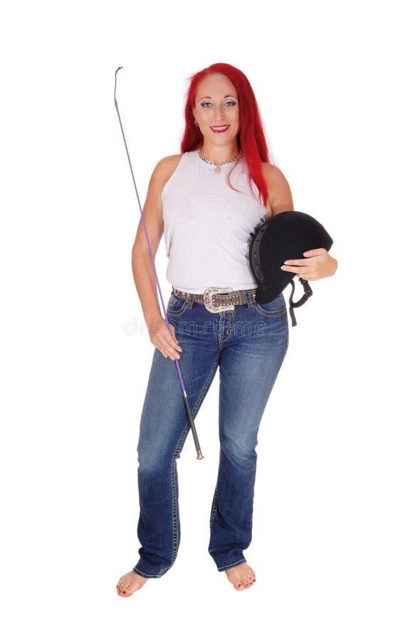 Uma mulher do cavaleiro de horseback com capacete foto de stock