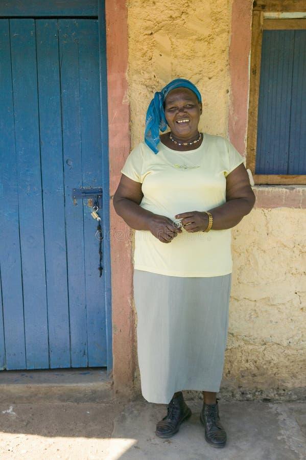 Uma mulher do Kenyan sorri na frente do programa de reabilitação de Pepo La Tumaini Jangwani, da comunidade de HIV/AIDS, do orfan imagens de stock royalty free