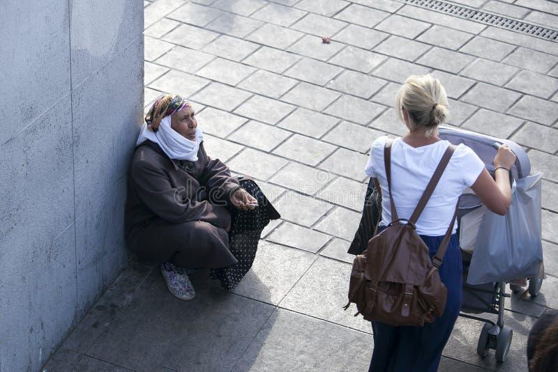 Uma mulher do mendigo em um lenço no cais foto de stock