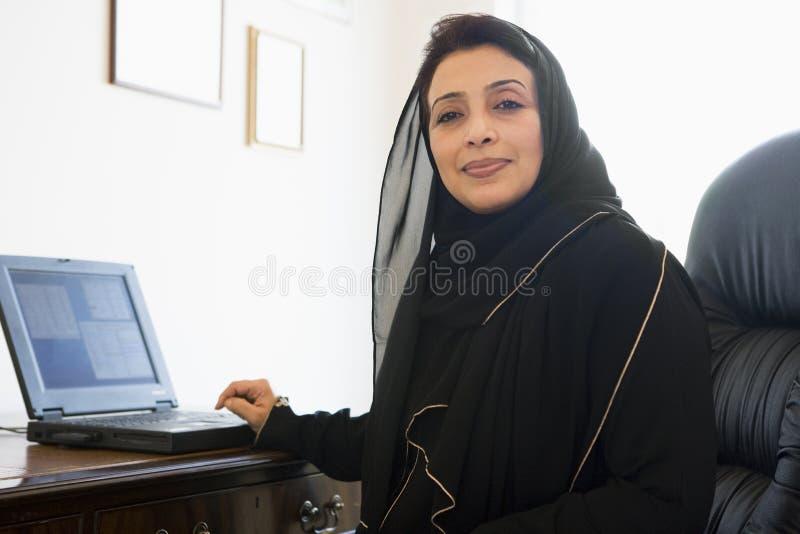 Uma mulher do Oriente Médio que usa o computador fotografia de stock