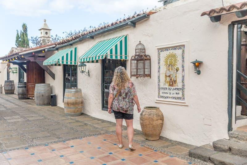 Uma mulher do turista procura algo no fora de um restaurante agradável e do vintage fotografia de stock royalty free