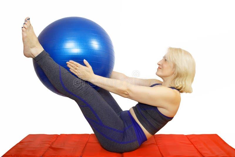 Uma mulher dos anos de idade 48 executa um exercício das compressas de um curso de Pilates que retrocedem a bola o fitball e aume imagem de stock royalty free
