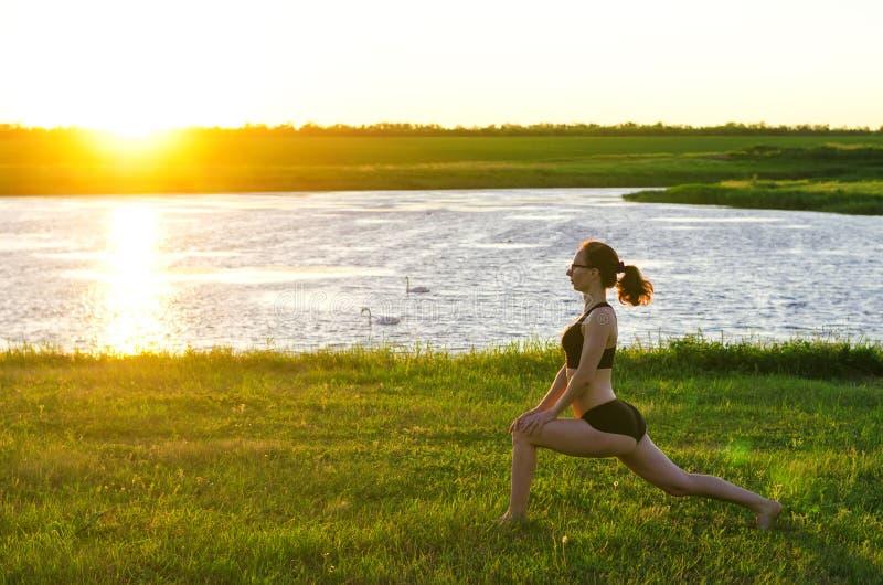Uma mulher dos esportes executa os exercícios no por do sol, uma cópia do livre fotografia de stock royalty free
