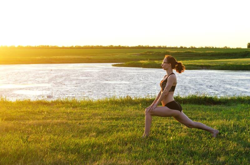 Uma mulher dos esportes executa os exercícios no por do sol, uma cópia do livre foto de stock