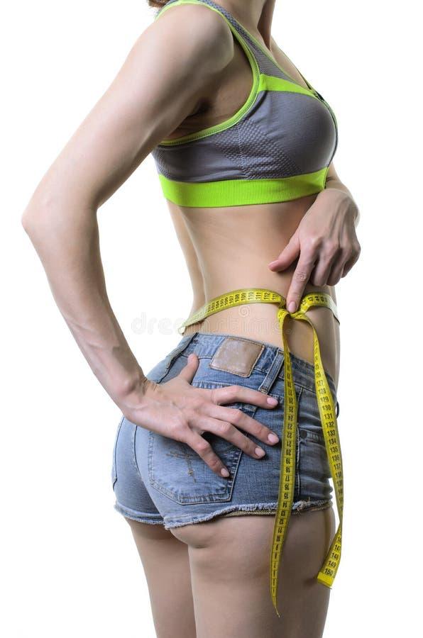 Uma mulher dos esportes mede a cintura, isolada em um backgroun branco fotos de stock