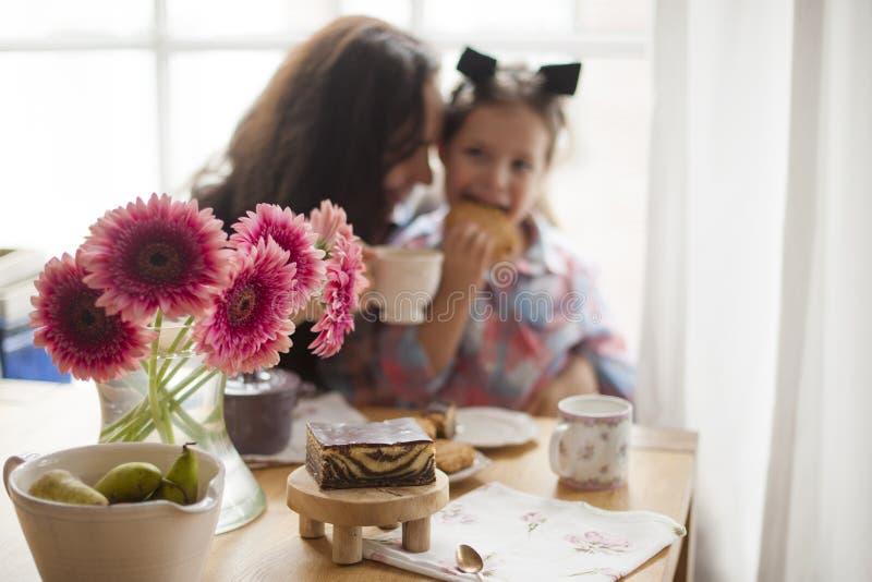Uma mulher e uma filha pequena estão comendo o café da manhã em casa em uma tabela pela janela Bom dia feliz da família e do café imagem de stock
