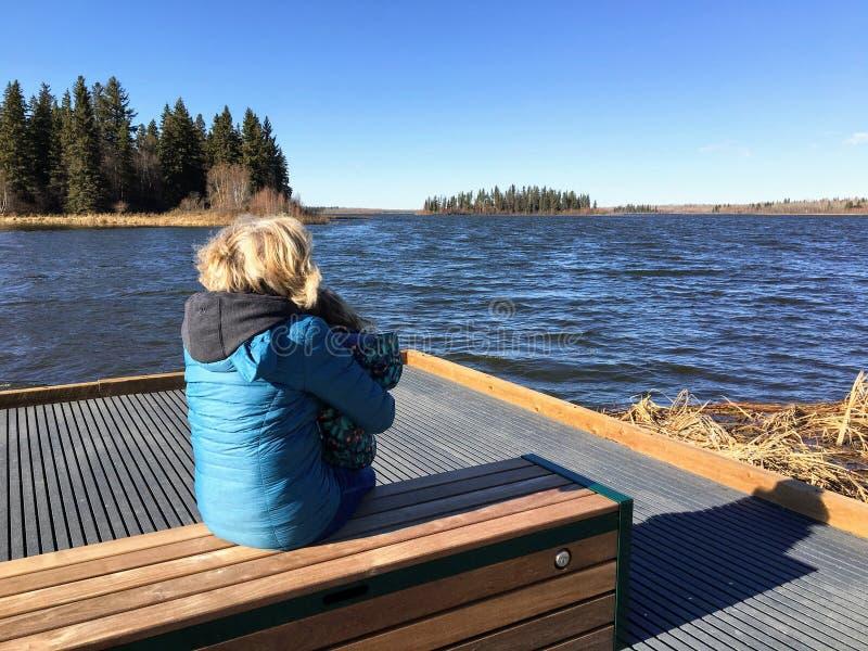 Uma mulher e sua neta que apreciam as vistas do lago bonito Astotin na ilha dos alces foto de stock