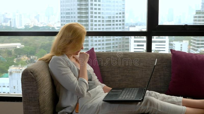 Uma mulher elegante está encontrando-se em um sofá pela janela panorâmico que negligencia os arranha-céus e que usa seu portátil imagens de stock royalty free