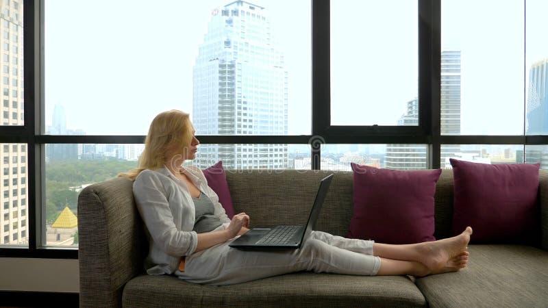 Uma mulher elegante está encontrando-se em um sofá pela janela panorâmico que negligencia os arranha-céus e que usa seu portátil foto de stock royalty free