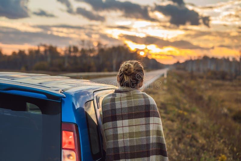 Uma mulher em uma manta está pelo carro no lado da estrada no fundo do alvorecer Conceito da viagem por estrada fotografia de stock royalty free