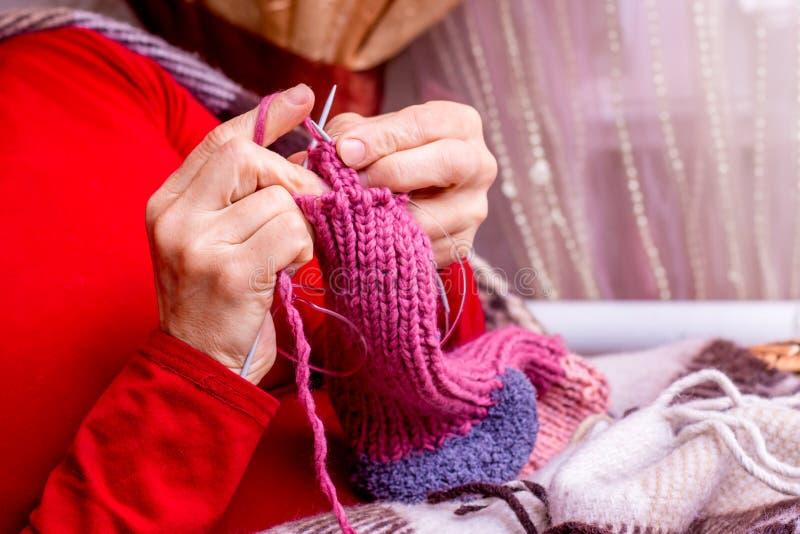 Uma mulher em um ajuste acolhedor da casa faz malha peúgas mornas para o winter_ fotos de stock