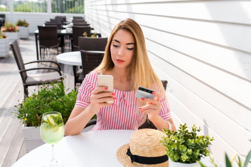 Uma mulher em um café no verão na cidade, paga o jantar do café da manhã do almoço, cartão de crédito plástico, aplicaç imagem de stock royalty free