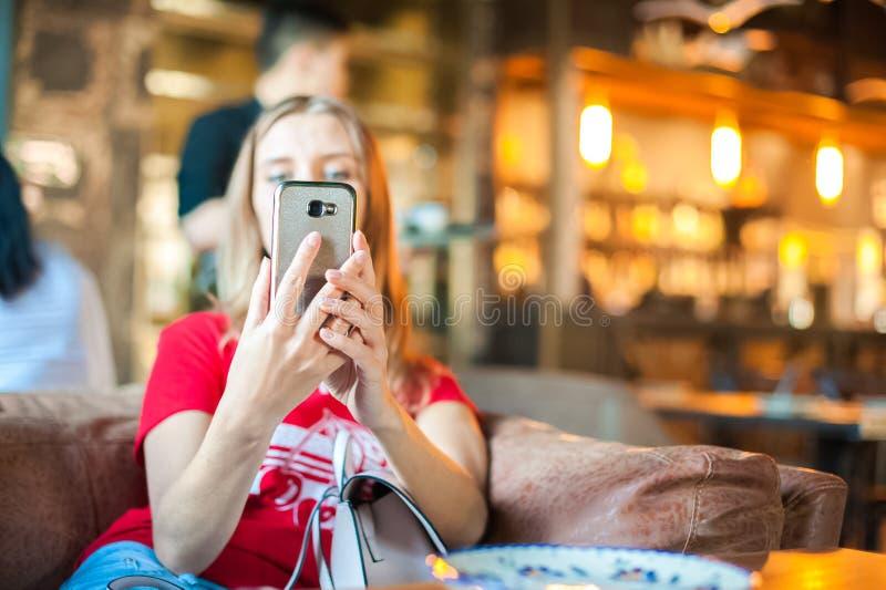 Uma mulher em um café em uma tabela faz o selfie no telefone Um visitante ao restaurante toma imagens dsi mesmo no telefone Mulhe fotografia de stock
