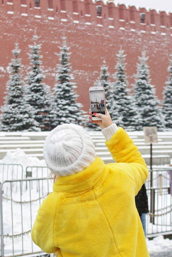 Uma mulher em um casaco de pele amarelo brilhante feito da eco-pele artificial, toma uma foto de uma foto em um quadrado vermelho imagens de stock royalty free