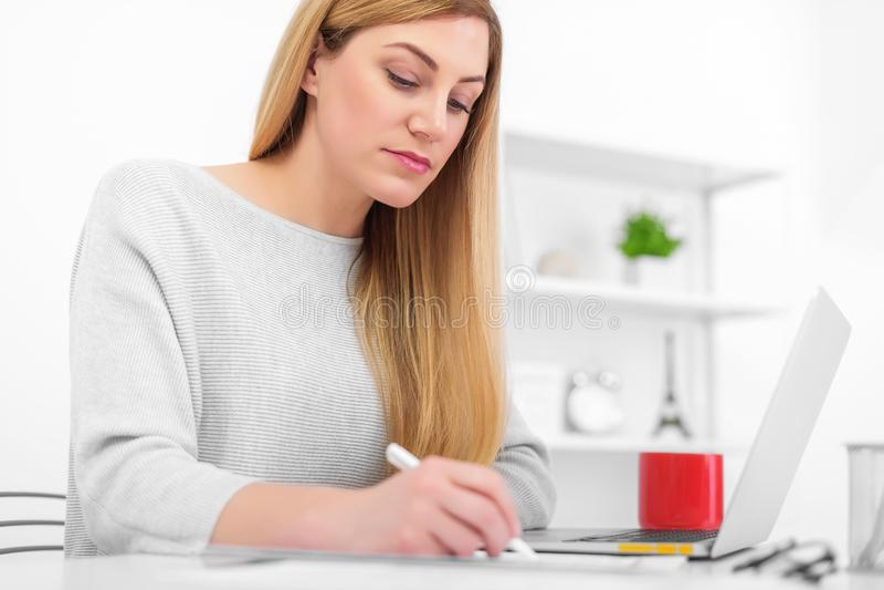 Uma mulher em um escritório branco está sentando-se em uma tabela e em uma escrita Uma jovem senhora que usa um portátil enche or fotografia de stock royalty free