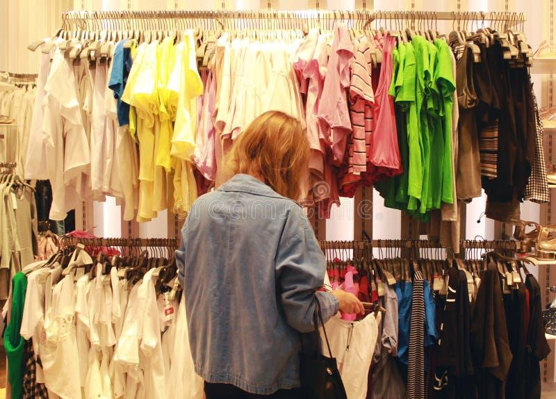 Uma mulher em um revestimento das calças de brim está comprando imagem de stock royalty free