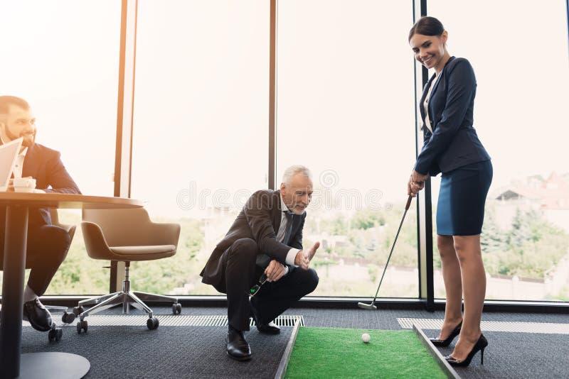 Uma mulher em um terno de negócio do preto joga o golfe no escritório Um ancião em um terno de negócio ajuda-a foto de stock royalty free