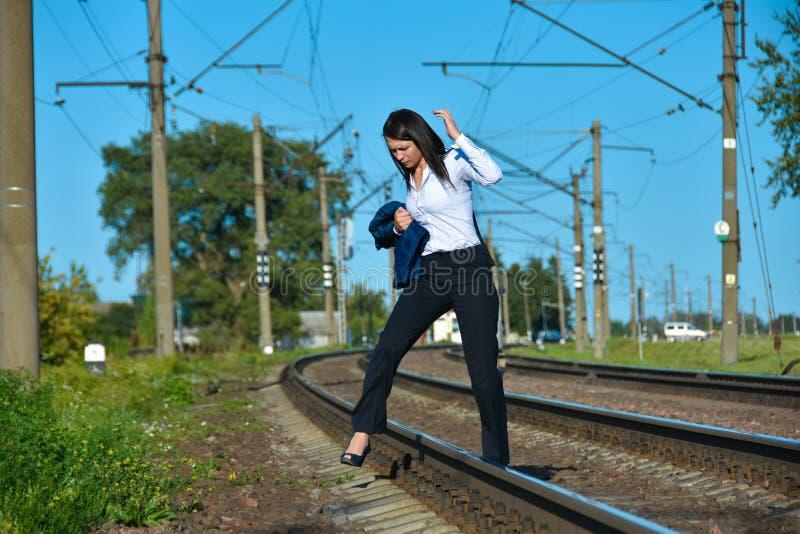 Uma mulher em um terno do escritório quebra as regras de tráfego e cruza a estrada de ferro em um lugar proibido durante o dia imagem de stock royalty free