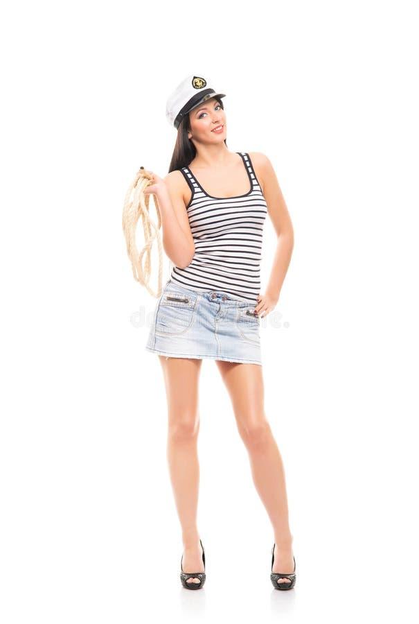 Uma mulher em um traje do marinheiro no branco imagem de stock royalty free