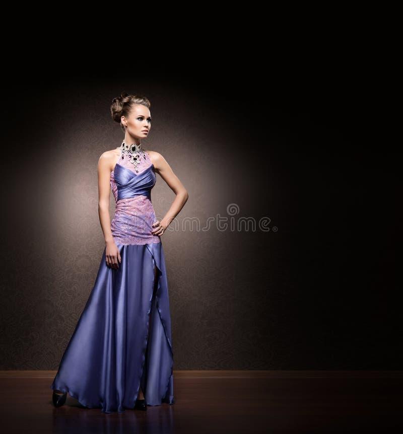 Uma mulher em um vestido e em uma joia azuis fotografia de stock