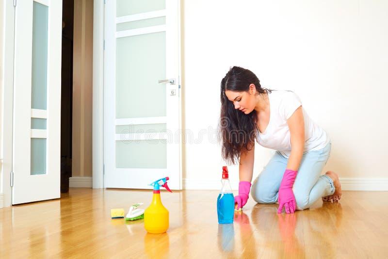 Uma mulher em uma sala da casa que limpa o assoalho no glov de borracha imagens de stock royalty free