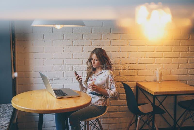 Uma mulher encantador com um sorriso bonito lê a boa notícia em seu telefone celular ao relaxar em um café, um caucasiano feliz imagens de stock royalty free
