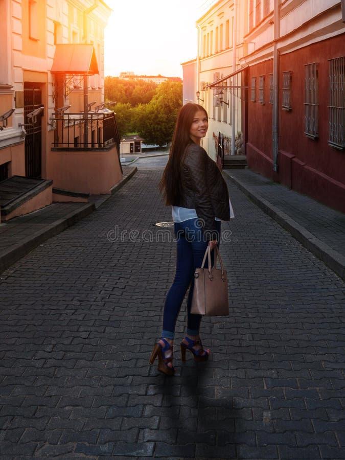 Uma mulher encaracolado bonita olha para trás, estando em uma rua estreita leve em um dia de verão Menina moreno à moda com saco imagens de stock
