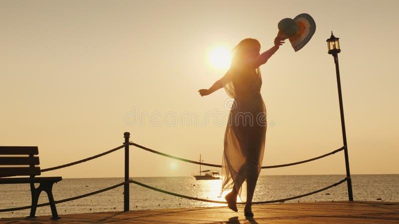 Uma mulher encontra o alvorecer no mar Emocionalmente girando com um chapéu em sua mão no cais Sonho do conceito do curso imagem de stock