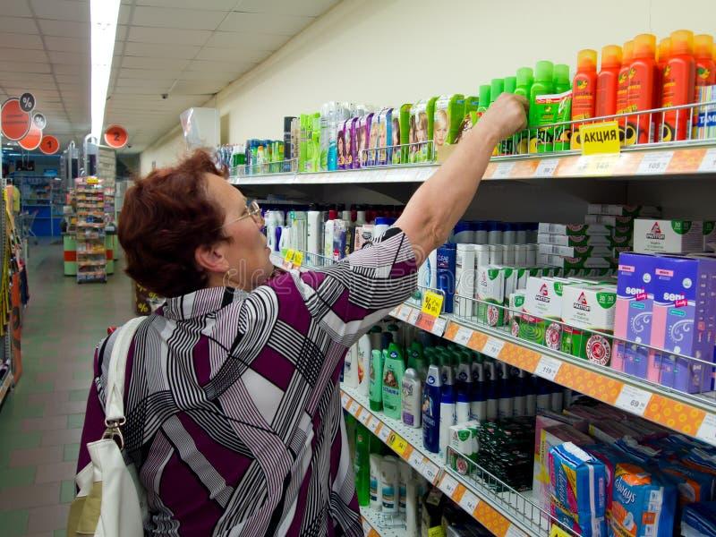 Uma mulher escolhe um champô nas prateleiras na loja imagens de stock