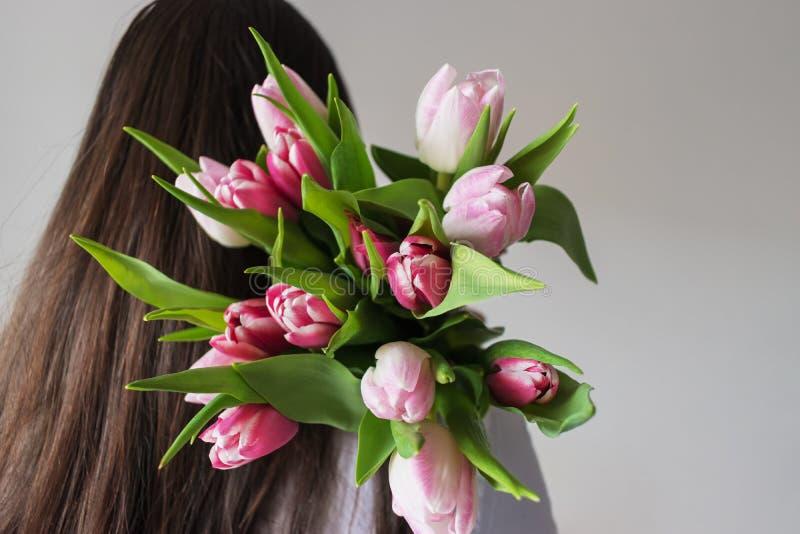 Uma mulher esconde um ramalhete das tulipas atrás dela para trás imagem de stock