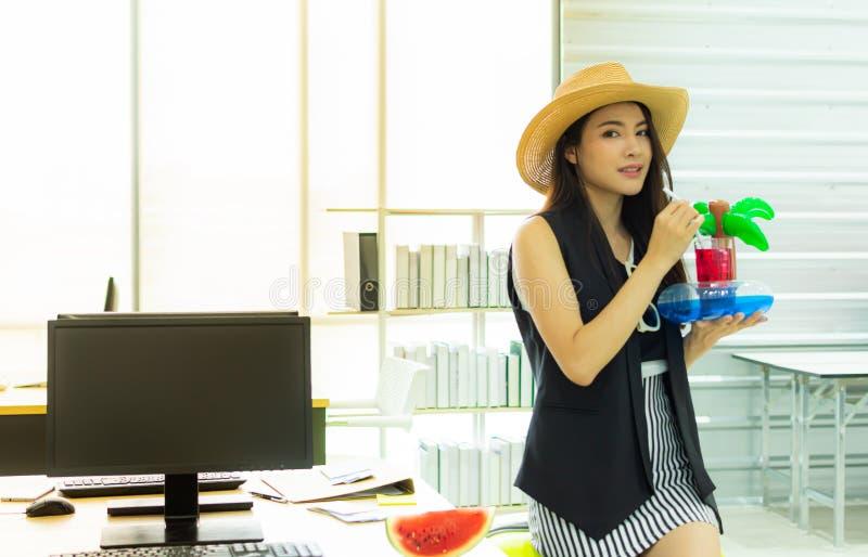 Uma mulher está bebendo o suco do watermalon no escritório foto de stock royalty free