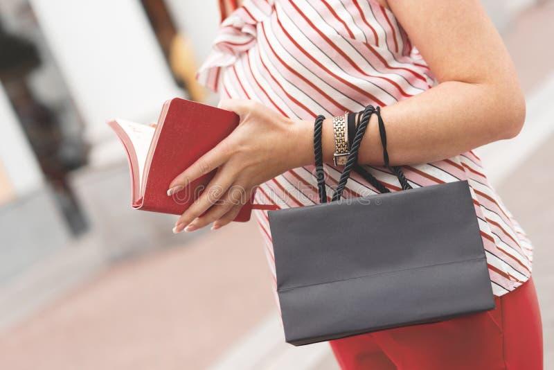 Uma mulher está com um saco de papel preto em seus mãos e caderno pequeno Conceito da compra Coral vivo Espaço para o texto no sa fotos de stock royalty free