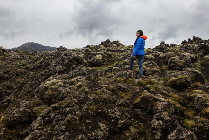 Uma mulher está em um campo de lava coberto de vegetação do musgo foto de stock