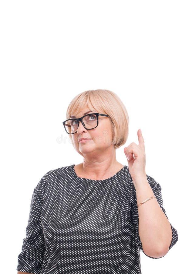 Uma mulher está estando pensativamente e está guardando um dedo indicador acima do close-up em um fundo isolado branco fotografia de stock