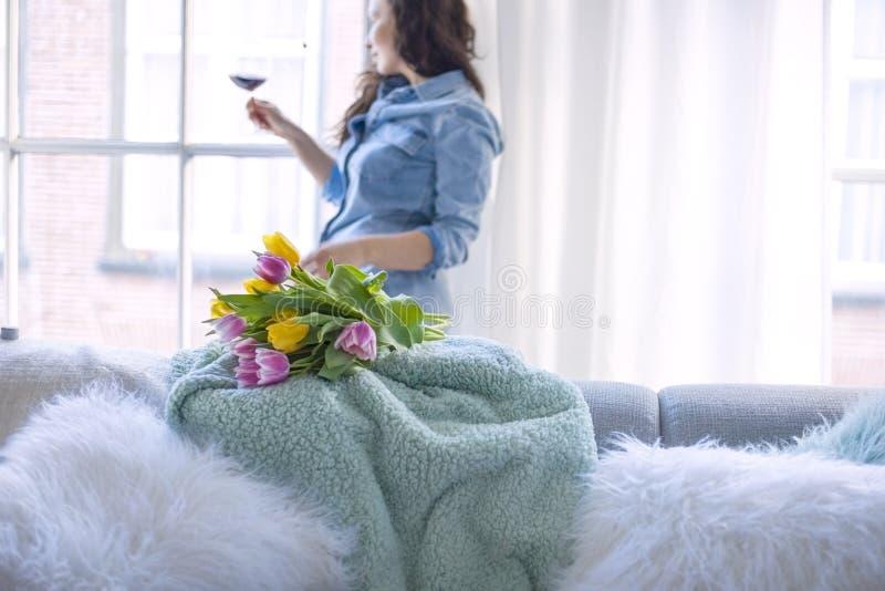 Uma mulher está guardando um vidro do vinho tinto e um ramalhete fresco de tulipas amarelas e cor-de-rosa Apenas chovido sobre Em foto de stock