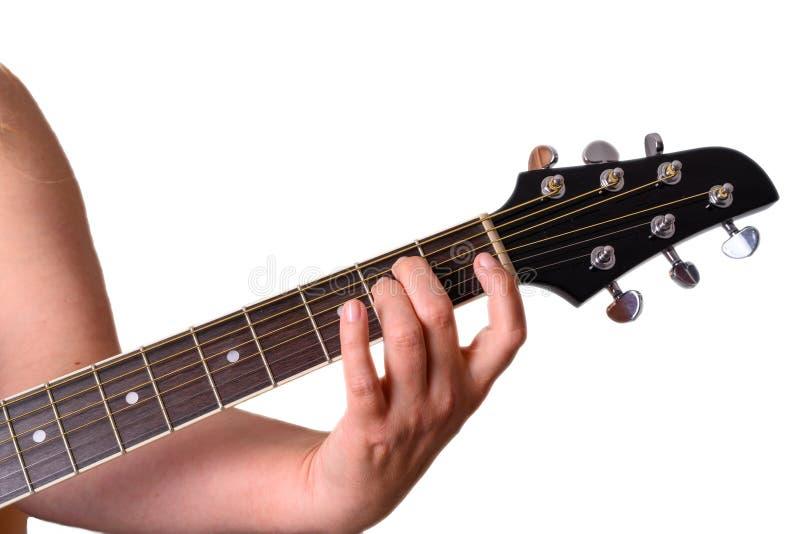 Uma mulher está jogando uma guitarra acústica imagens de stock royalty free