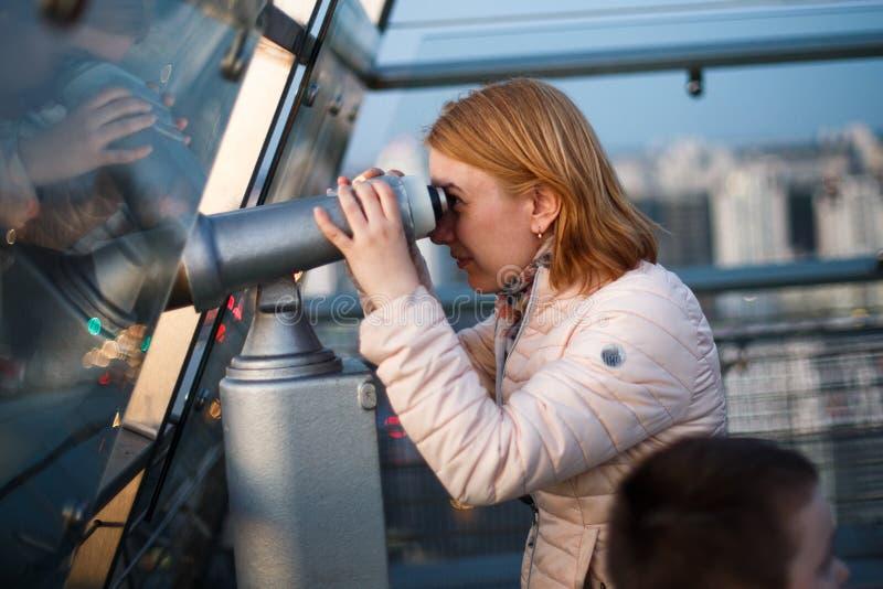 Uma mulher está olhando através de um telescópio fotografia de stock royalty free
