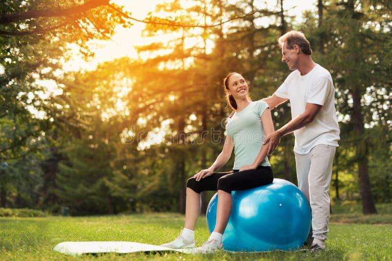 Uma mulher está sentando-se em uma bola para a ioga Um homem está estando de trás e está olhando-a imagens de stock