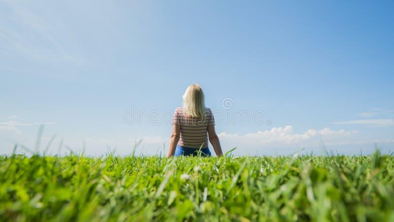 Uma mulher está sentando-se na grama tosquiado perfeita que entra em um céu azul claro fotografia de stock
