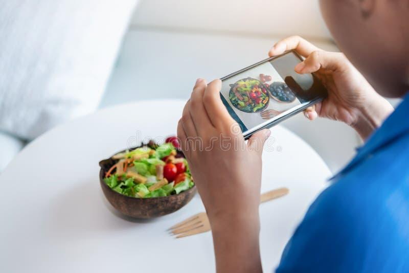 Uma mulher está usando smartphones para tomar fotos para afixar uma salada ela fotografia de stock