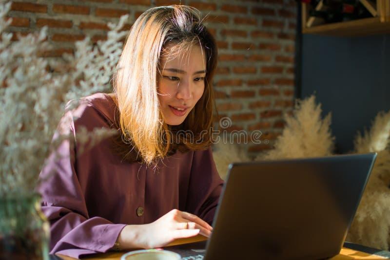 Uma mulher est? comprando no Internet ao p?r pouco sorriso sobre sua cara fotografia de stock
