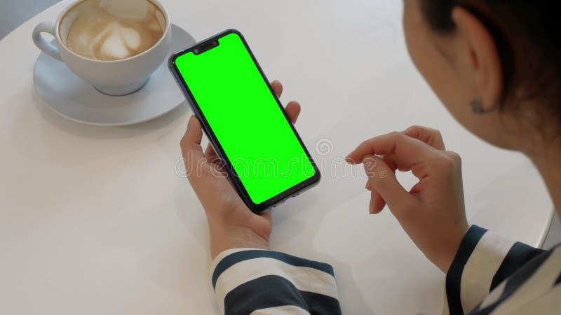Uma mulher est? falando a um amigo sobre um v?deo chama um smartphone da verde-tela imagem de stock royalty free