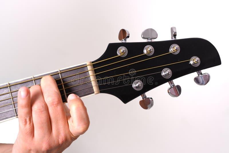 Uma mulher est? jogando uma guitarra ac?stica imagem de stock