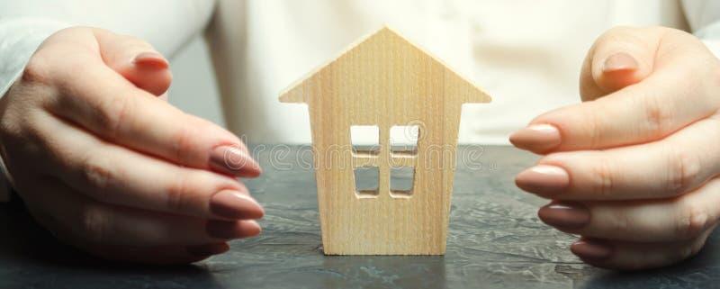 Uma mulher est? protegendo uma casa de madeira diminuta Conceito do seguro patrimonial Prote??o do alojamento seguran?a e seguran fotos de stock