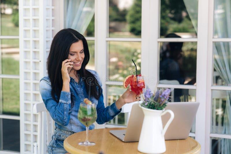 Uma mulher europeia bonita de brilho que guarda um cocktail em sua mão, sorrindo, falando no telefone com uma amiga fotos de stock royalty free