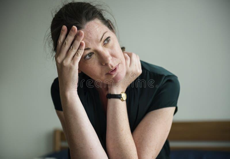 Uma mulher fatigante que tem uma dor de cabeça imagem de stock