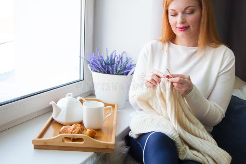 Uma mulher faz malha com as agulhas de confecção de malhas do fio branco Bebe t fotografia de stock