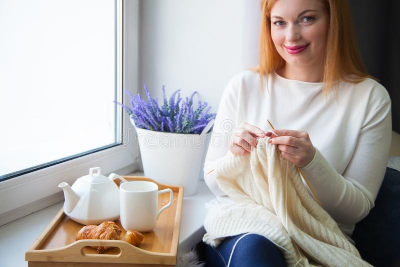 Uma mulher faz malha com as agulhas de confecção de malhas do fio branco Bebe t fotos de stock