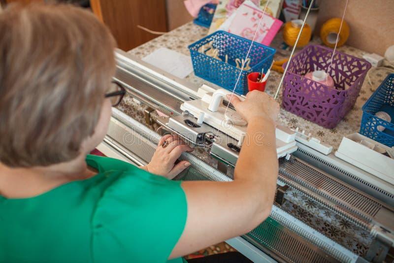 Uma mulher faz malha em uma máquina de confecção de malhas, foto de stock