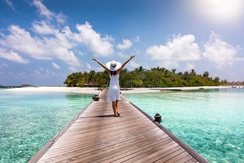 Uma mulher feliz anda abaixo de um cais de madeira em Maldivas imagem de stock
